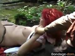 Redhead bondage slave fucked by medieval bandits in the woods