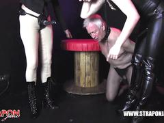 Femdoms in latex dominate tag team sissy slut face fuck strapons and spunk into doggy bowl