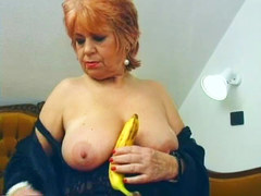 Granny inserts banana in her pussy